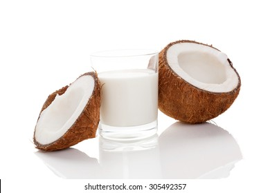 Coconut milk in glass and cracked coconut isolated on white background. Vegan milk drinking concept.