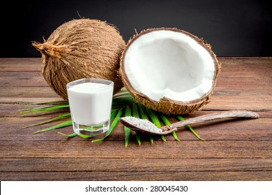 Coconut and coconut milk in glass on wooden table