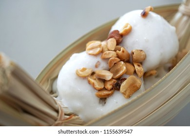 Coconut milk ice cream with nuts topping in leaf bowl on white table, Thai dessert style