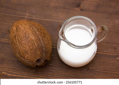 Coconut milk in jug on wooden table seen from above