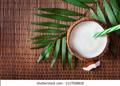 Coconut milk in a nut shell with a drinking straw