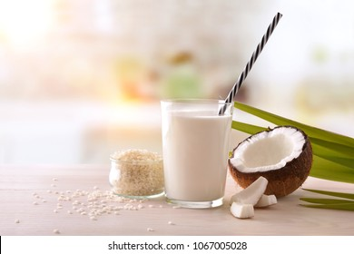 Coconut milk and rice in glass with fruit and cereal on wooden table on a white kitchen background. Alternative milk concept. Front view. Horizontal composition.