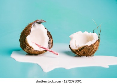 Coconut milk with a straw on turquoise background. Half of coconut on blue background. Tropical fruit concept