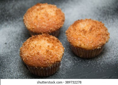 Coconut muffin on black plate with utensils.