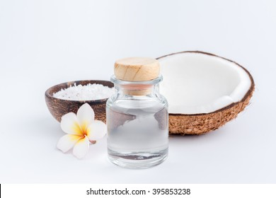 coconut oil in a bottle, background is a half of coconut, isolated
