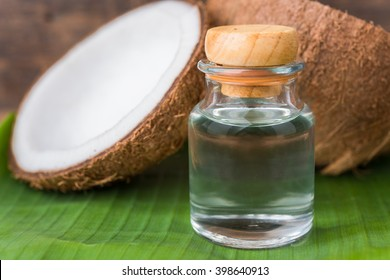 coconut oil in a bottle, background is a half of coconut on a banana leaf