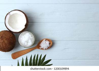 coconut oil, coconuts and green tropical leaves on wooden background. Top view.
