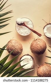 Coconut oil and coconuts on a background with tropical leaves.