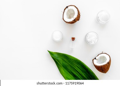 Coconut oil cosmetics for skin and hair care. Oil in small bottle, cream jar, halfs of coconut with shelf, palm leaves on white background top view.