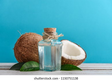 Coconut oil with fresh coconut for alternative therapy on blue background