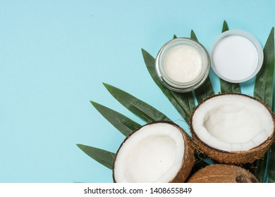 Coconut oil with fresh cocnut, natural cosmetic, flat lay image on blue.