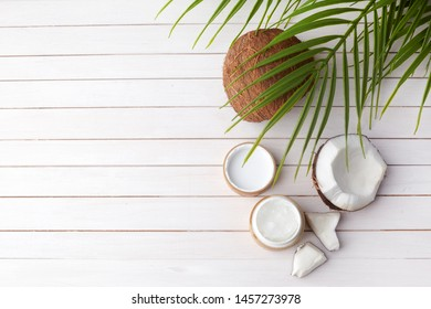Coconut oil with fresh cocnut, natural cosmetic, flat lay image on wooden background