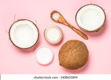 Coconut oil with fresh cocnut and tropical leaves, natural cosmetic, flat lay image on pink.