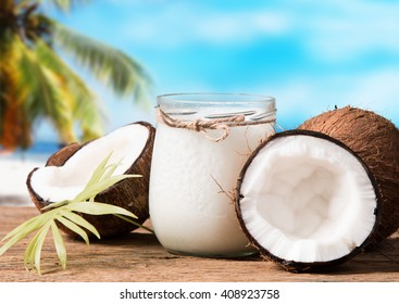 coconut oil and fresh coconuts on old wooden table with tropical beach background