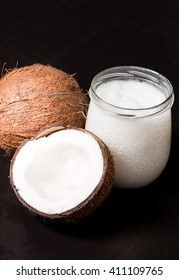coconut oil and fresh coconuts on black stone