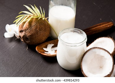 coconut oil and fresh coconuts on black stone background