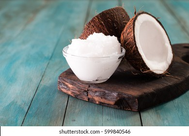 coconut oil and fresh coconuts on old wooden table