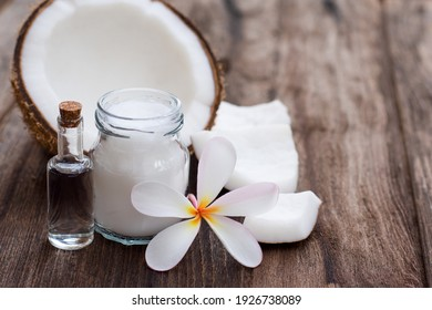 Coconut oil and fresh coconut fruit on wooden table background. Closeup.