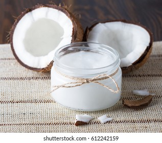 Coconut oil in glass jar and fresh coconut