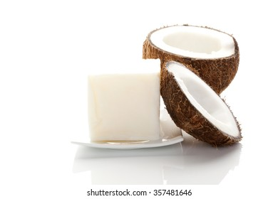 Coconut oil. Hard coconut oil and coconut isolated on white background with reflection. Healthy eating and cooking.