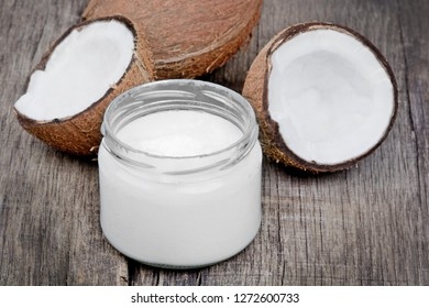 Coconut oil in a jar and coconut fruits on old wood table
