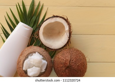 Coconut oil. Natural pure coconut oil and fresh coconuts in a section on a palm leaf on a yellow wooden plank background. cosmetics with coconut extract. Organic Natural Cosmetics
