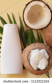 Coconut oil. Natural pure coconut oil and fresh coconuts in a section on a palm leaf on a yellow wooden plank background. cosmetics with coconut extract.