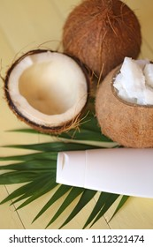 Coconut oil. Natural pure coconut oil and fresh coconuts in a section on a palm leaf on a yellow wooden plank background. cosmetics with coconut extract. Organic Cosmetics