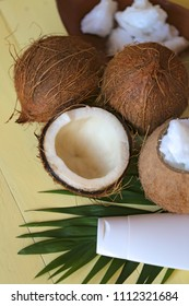 Coconut oil. Natural pure coconut oil and fresh coconuts in a section on a palm leaf on a yellow wooden  background. cosmetics with coconut extract. Organic Natural Cosmetics