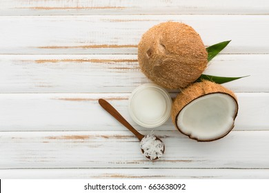 Coconut with coconut oil on white wooden table background. Good for package design element