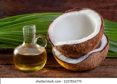 Coconut and coconut oil on wood background.