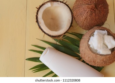 Coconut oil.  pure coconut oil and fresh coconuts in a section on a palm leaf on a yellow wooden plank background. cosmetics with coconut extract. Organic Natural Cosmetics