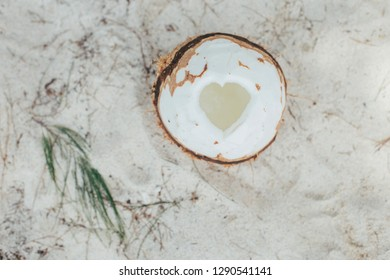 Coconut on the beach with shape of heart. Coconut milk and water on vacation