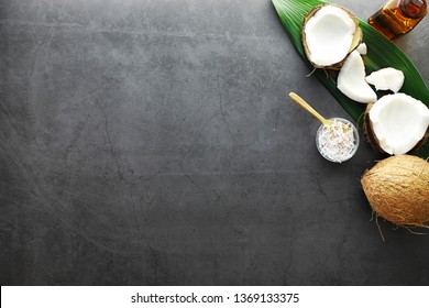 Coconut on a dark stone table. Coconut oil and chips.