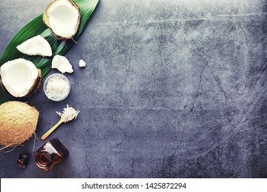 Coconut on a dark stone table. Coconut oil and spoon.