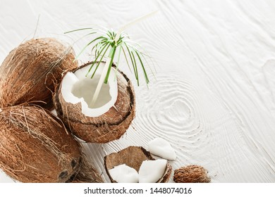 Coconut on a white wooden background, summer, heat, tropical style, coconut water, milk, oil, broken coconut, half coconut pulp, top view, copy space, place for your text, isolated on white background
