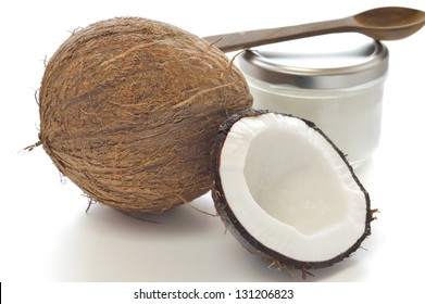 Coconut and organic coconut oil in a glass jar on white background.