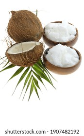 Coconut organic pure oil. Coconut oil in a wooden cup and coconuts fruits close-up with green  leaf isolated on white background.