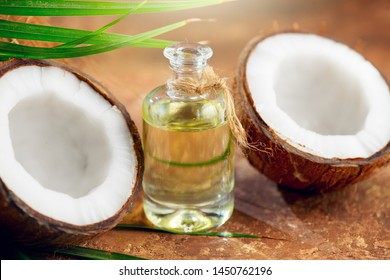 Coconut palm oil in a bottle with coconuts and green palm tree leaf on brown background. Coco nut closeup. Healthy Food, skin care concept. Vegan food. Skincare treatments. Vegan food. Aromatherapy