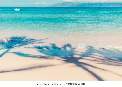 Coconut Palms Cast Shadows On The Beach And Tranquil Waters Of Kapalua Bay With Molokai In The Background On The Island Of Maui