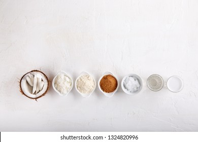 Coconut Products - coconut oil, water, milk, sugar, flakes and flour on white background. Top view. Copy space.