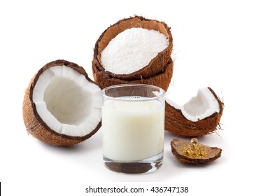 Coconut products.Coconut milk in a glass with coconut shells,oil in capsules and flakes isolated on white. Selective focus