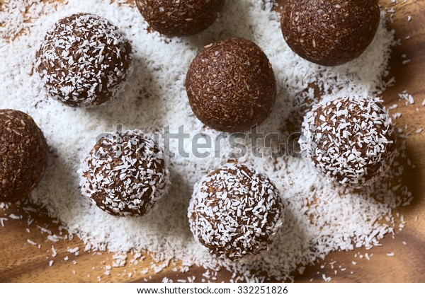Coconut rum balls being covered with grated coconut on wooden plate, photographed overhead with natural light (Selective Focus, Focus on the top of the balls)