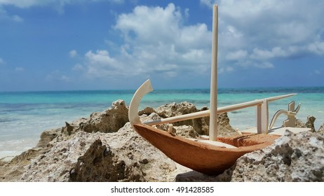 coconut shell boat toy on the rock and beach sea
