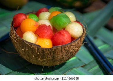 a coconut shell filled with a fruit salad with balls of different colors