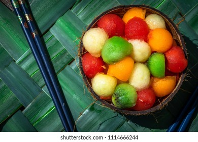 a coconut shell filled with a fruit salad with marbles of all colors
