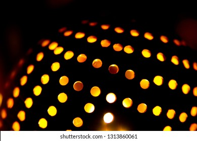 Coconut shell lamp with holes casting spotty light pattern on the wall