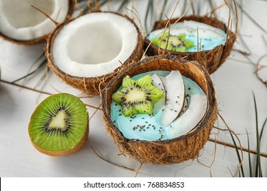 Coconut shell with yummy spirulina smoothie on wooden table. Healthy vegan food concept