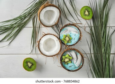 Coconut shells with yummy spirulina smoothie on wooden table. Healthy vegan food concept