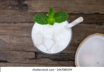 Coconut smoothies white fruit juice milkshake blend beverage healthy high protein the taste yummy In glass drink episode morning on a wooden background from top view.